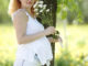 Happy Pregnant Woman with white chrysanthemas outdoors