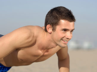 Handsome guy doing push-ups on Santa Monica Beach